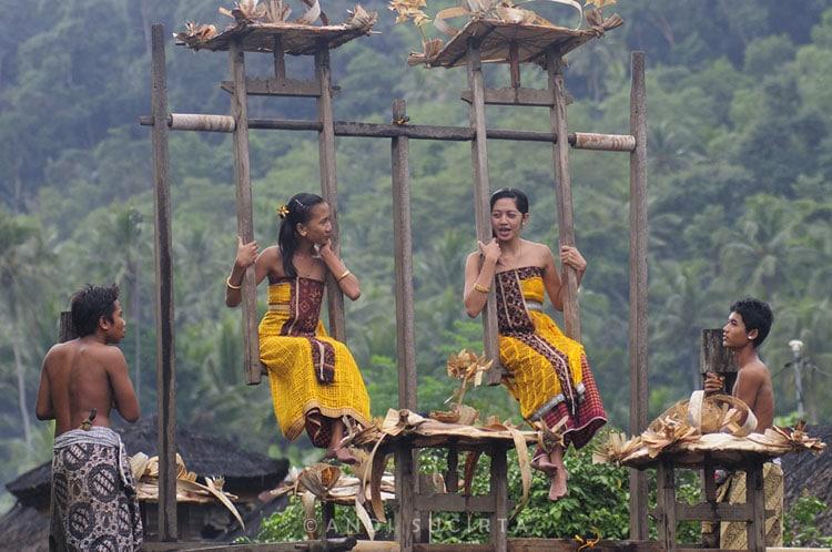 Au village de Tenganan, de très anciennes traditions perdurent. Ici, deux jeunes filles conversent au cours d'un rite traditionnel, durant lequel les garçons inculquent le mouvement à la balancelle, symbolisant ainsi l'équilibre. (Crédit photo : www.andisucirta.com)